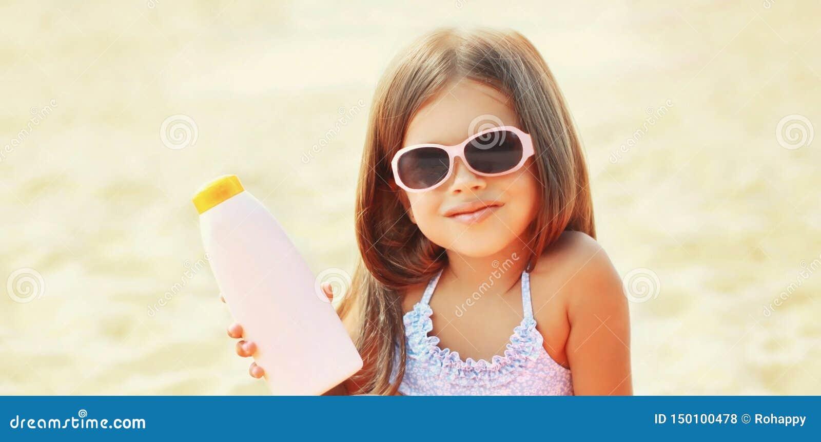Kind des kleinen Mädchens der Sommerporträtnahaufnahme auf dem Strand, der Lichtschutzhautflasche zeigt