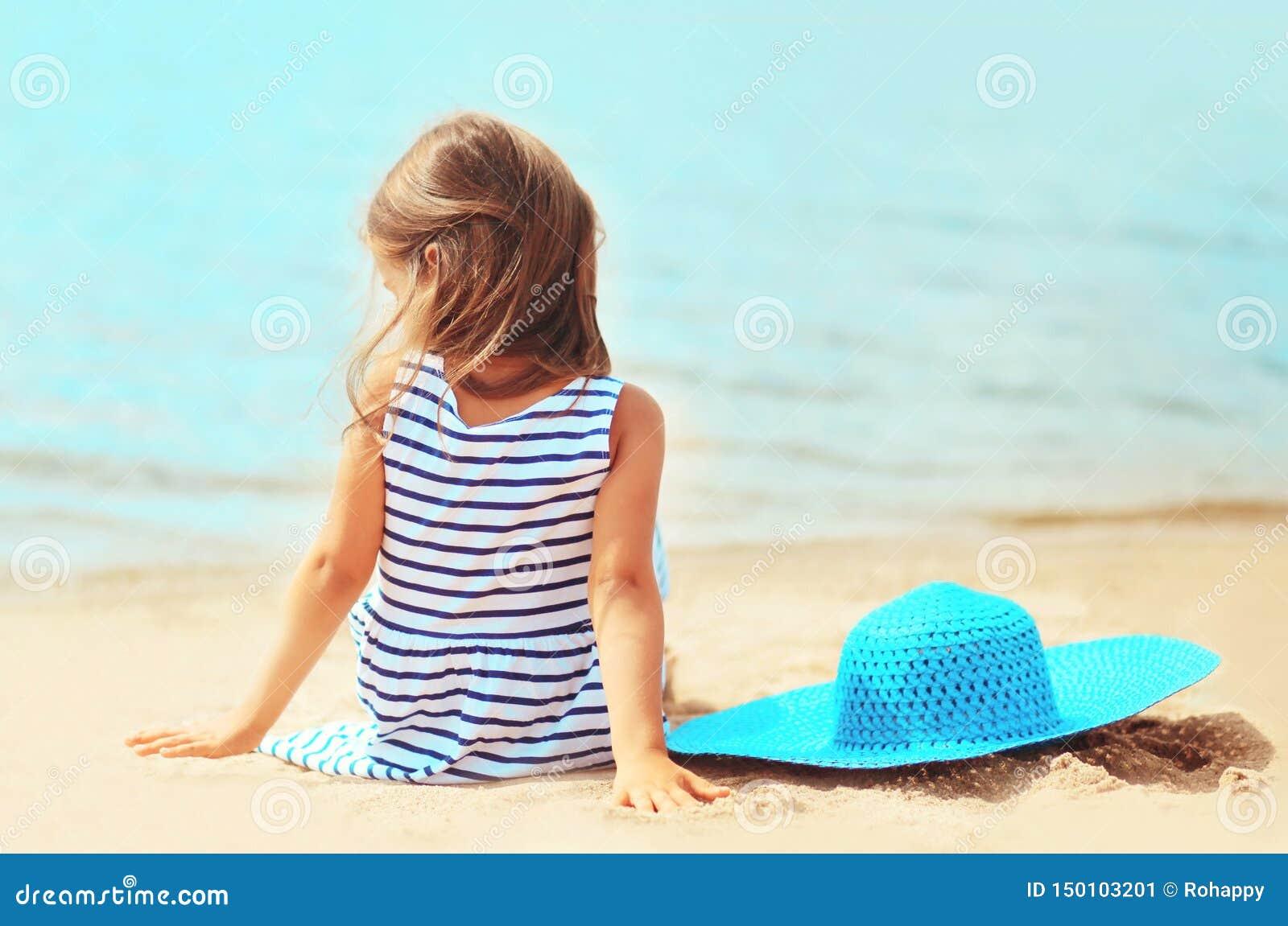 Kind des kleinen Mädchens in gestreiftem Kleid mit dem Sommerstrohhut, der auf Sandstrand sitzt