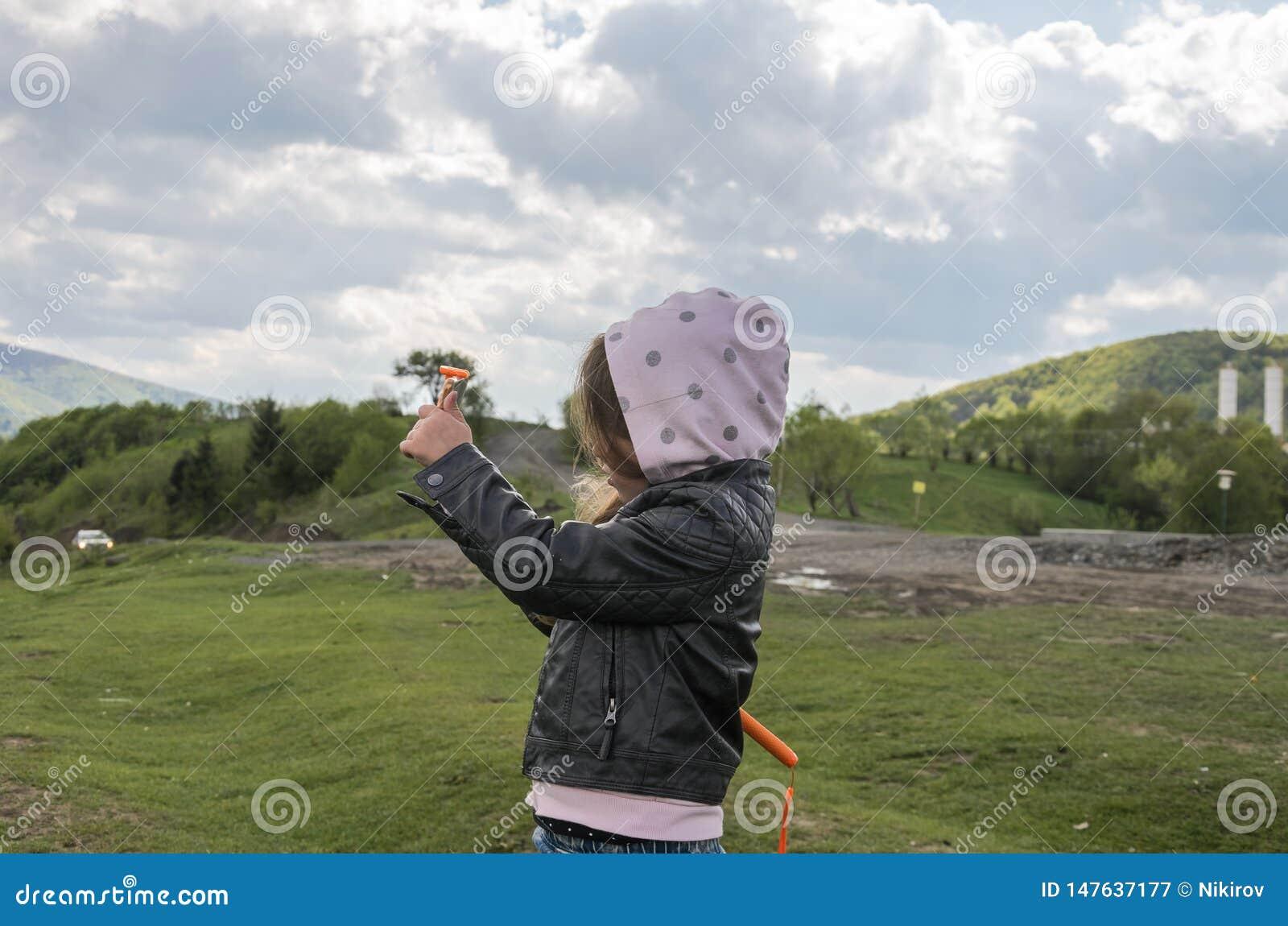 Kind des kleinen Mädchens macht Fotos am Telefon des Berges beim Reisen