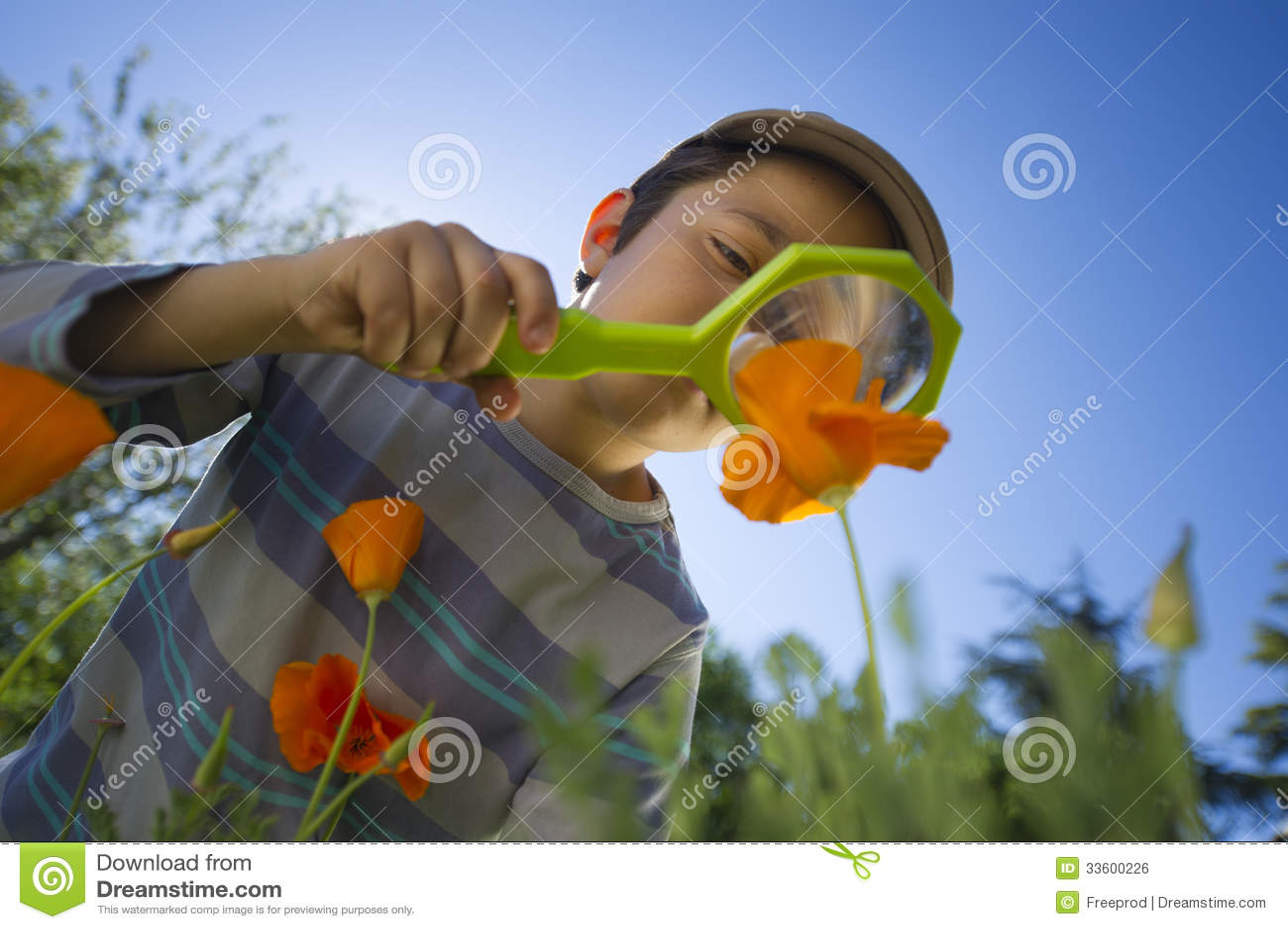 Kind die aard met een vergrootglas waarnemen