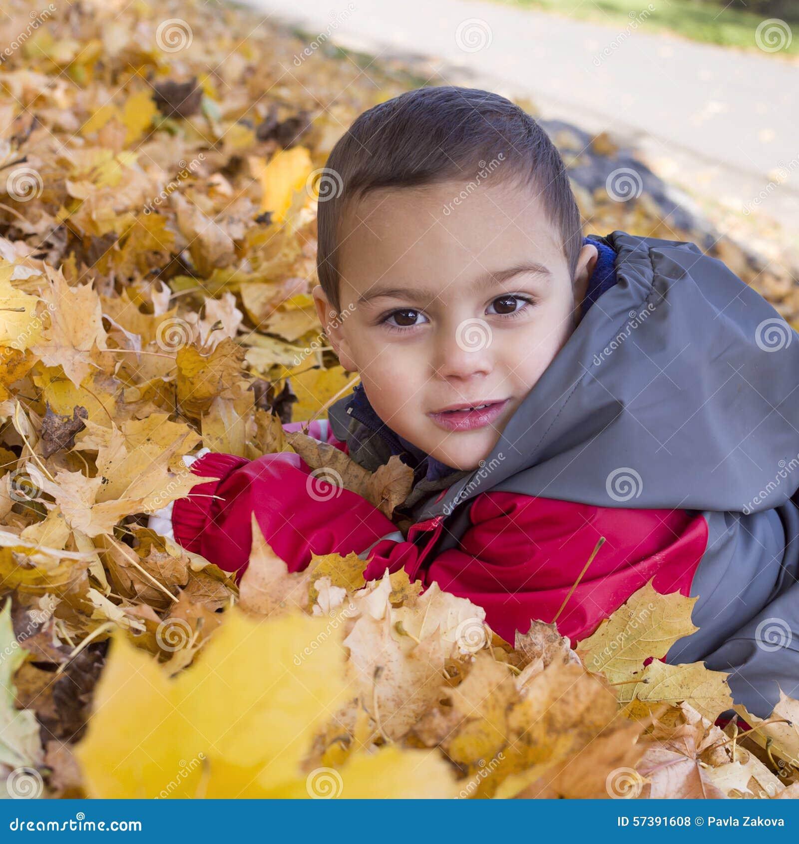 Kind die in de herfstbladeren leggen