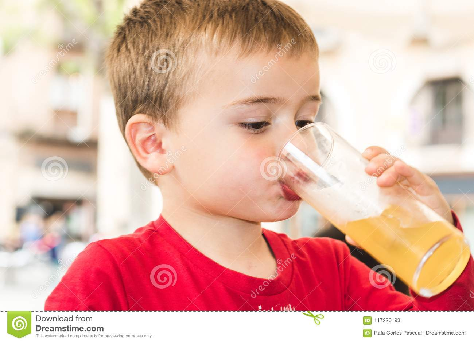 Kind die een soda in een glas drinken
