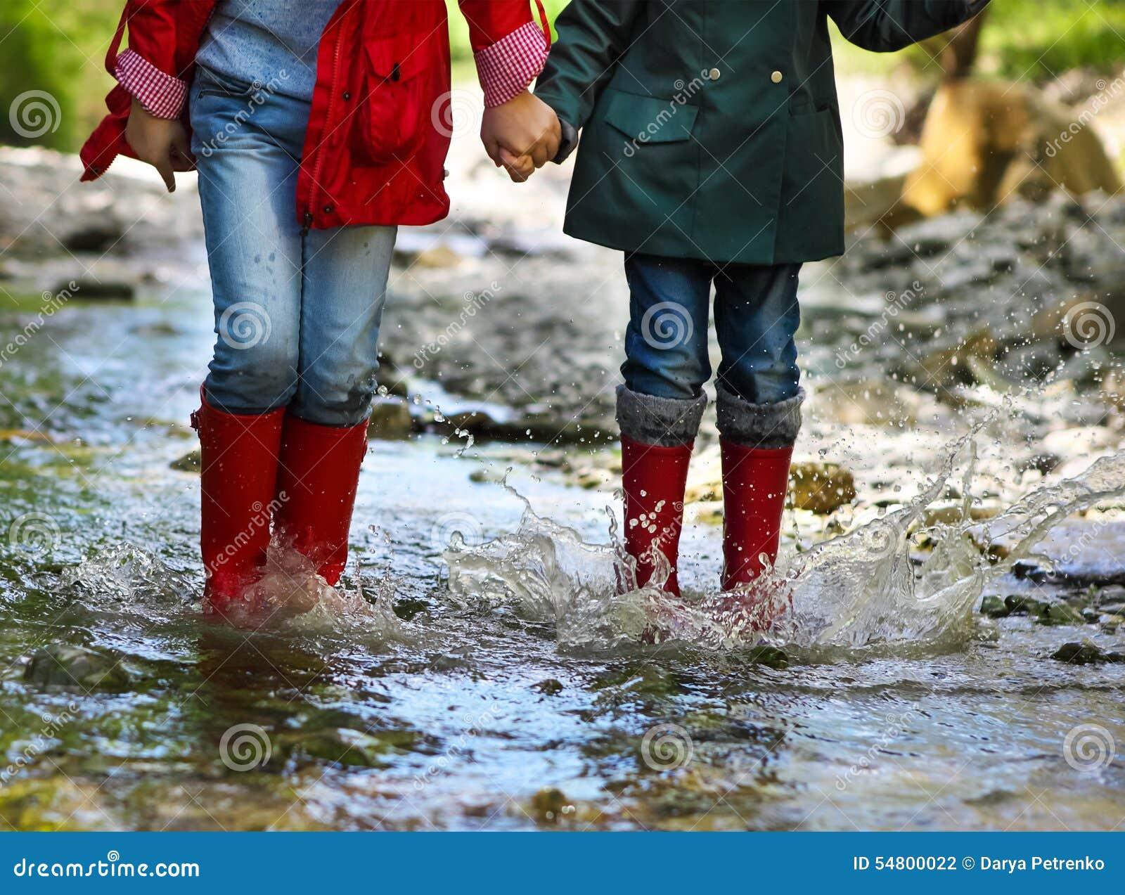 Kind die regenlaarzen het springen dragen Sluit omhoog