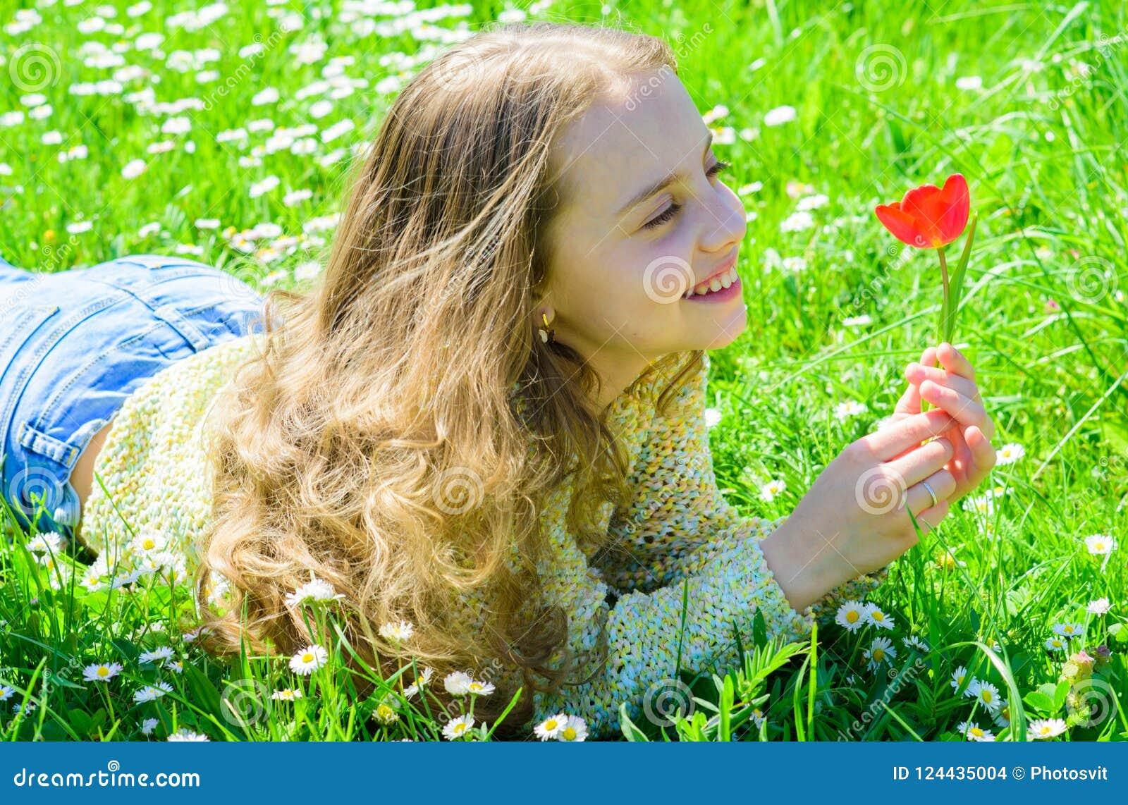 Kind genießen Duft der Tulpe beim Lügen an der Wiese Mädchen mit dem langen Haar, das auf grassplot, Grashintergrund liegt allerg