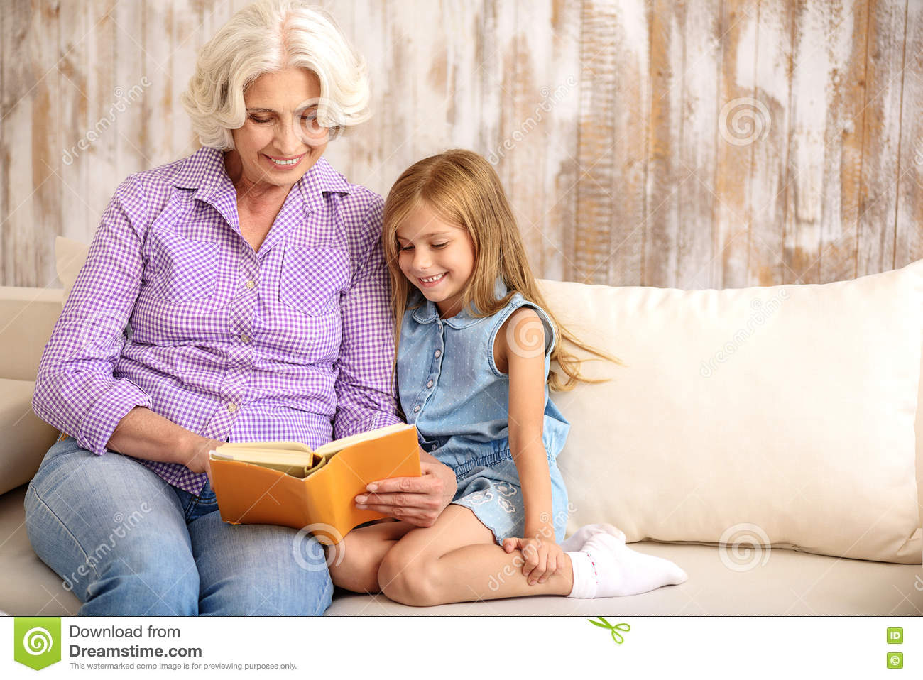 Kind granny and girl entertaining with book at home