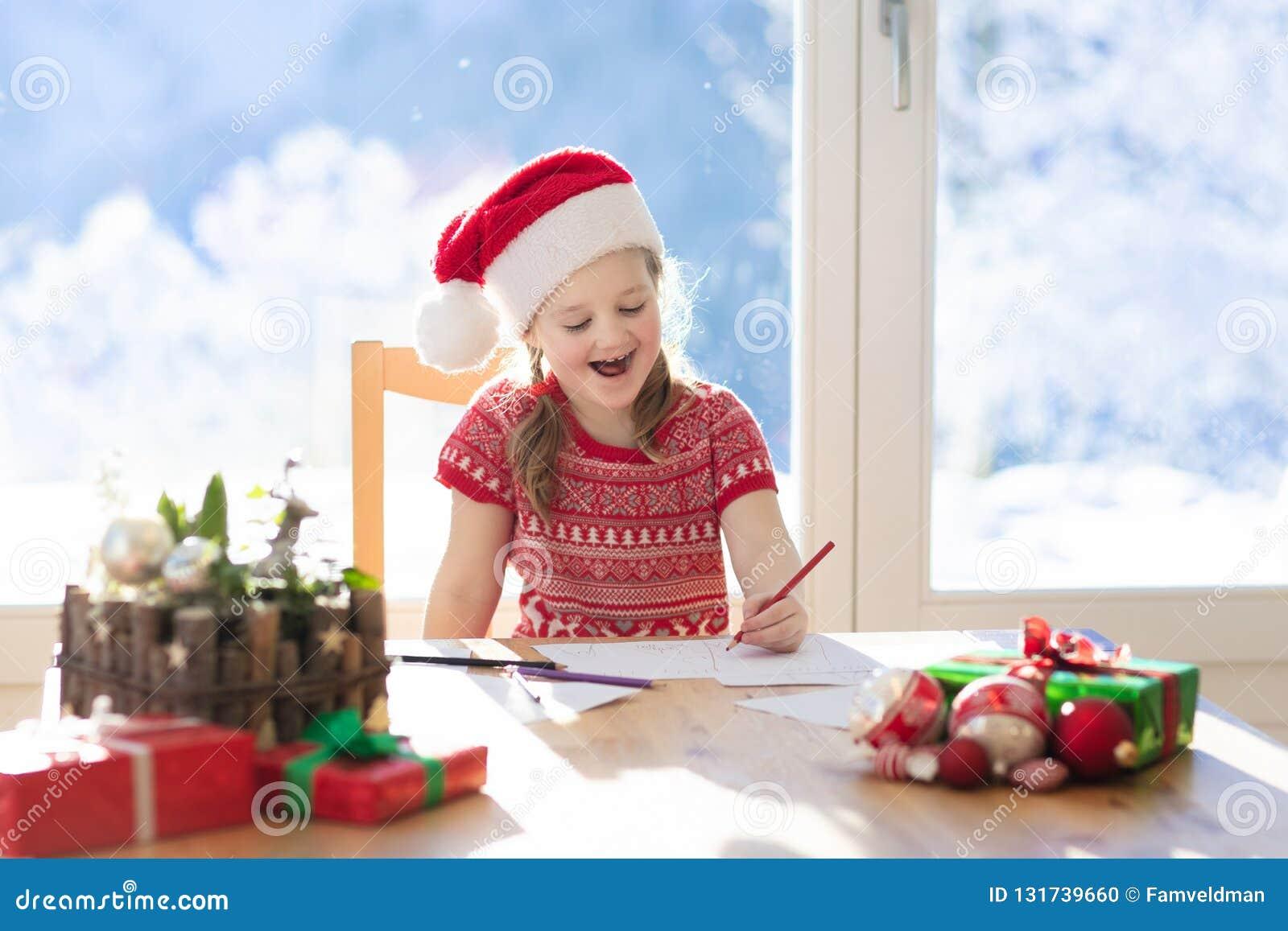 Kind het schrijven brief aan Kerstman op Kerstmisvooravond De jonge geitjes schrijven Kerstmis huidige het Meisjezitting van de w