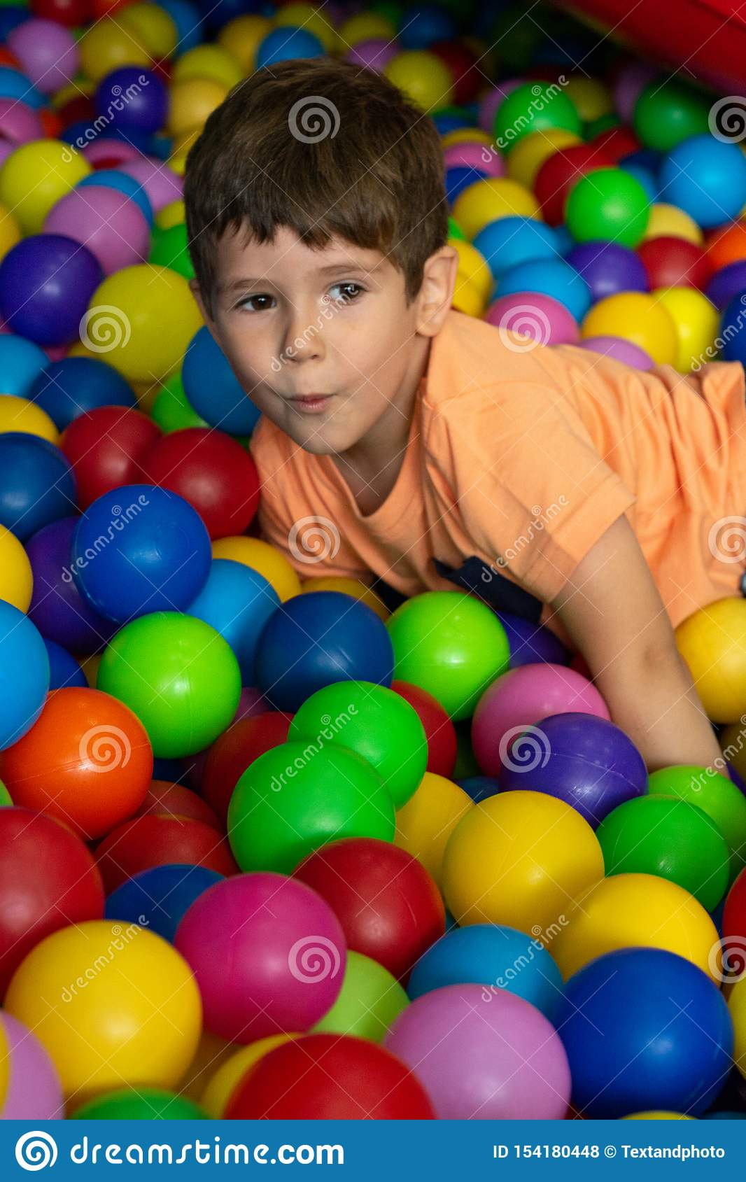 Kind het spelen met kleurrijke ballen in de pool van de speelplaatsbal Activiteitenspeelgoed voor weinig jong geitje De emotie di