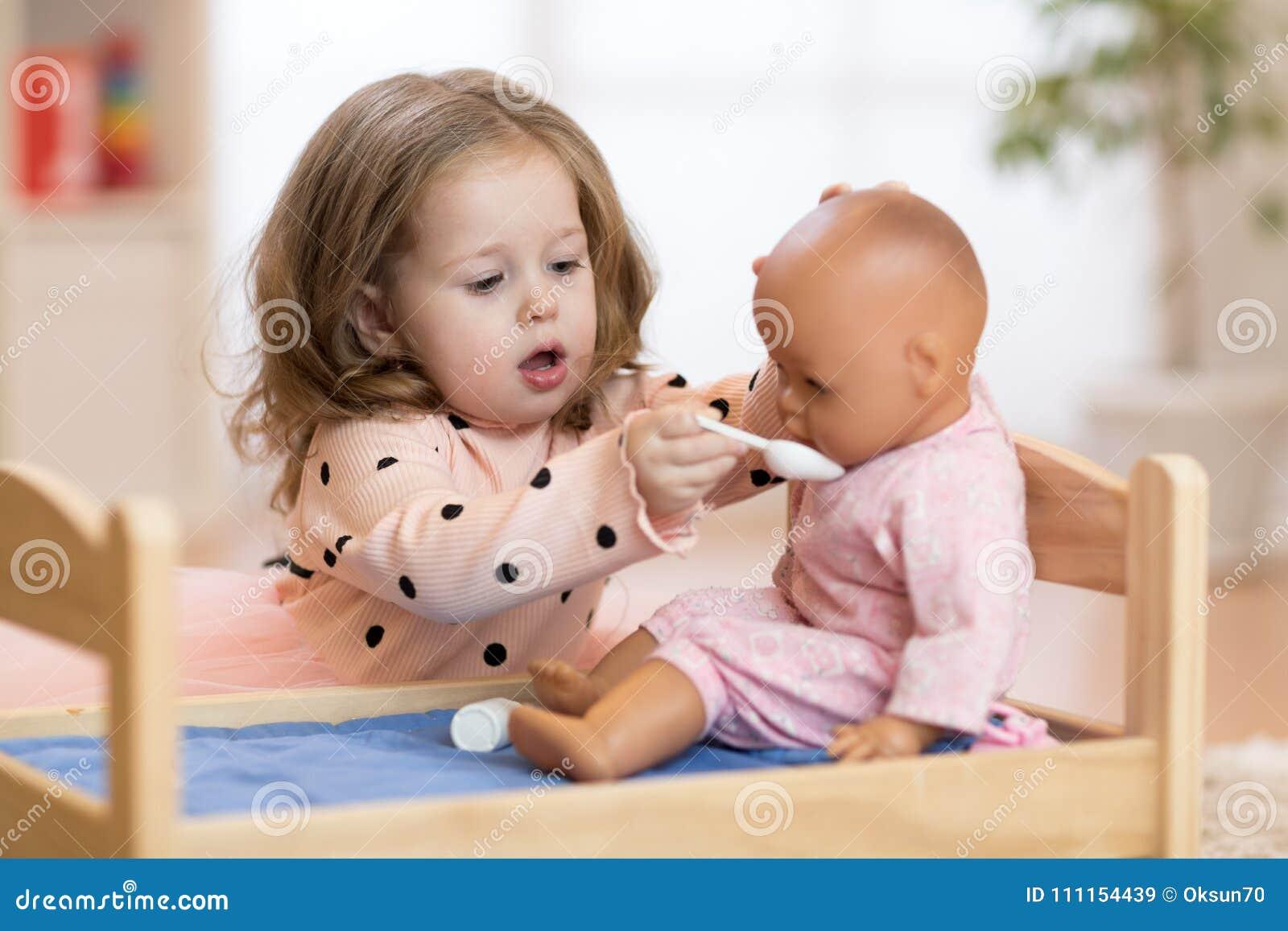 Kind im Kindergarten Kind im Kindergarten Kleines Kleinkind, das mit Puppe spielt
