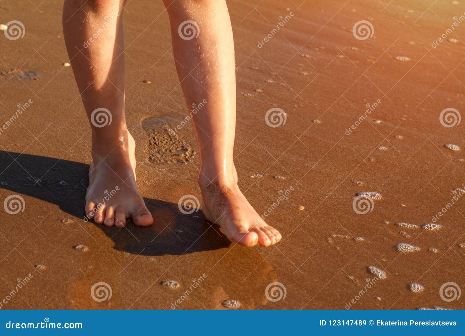 Kind läuft auf der Brandung auf dem Strand im Wasser