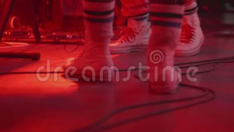A kind of legs in white sneakers. Artists on stage sing stock video footage
