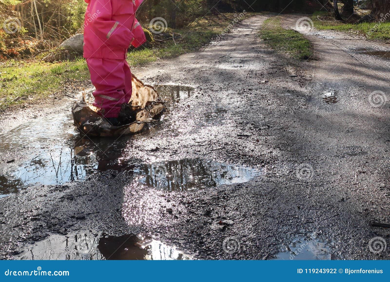 Kind/meisje met de roze pool/de vulklei van het regenkledings springende water