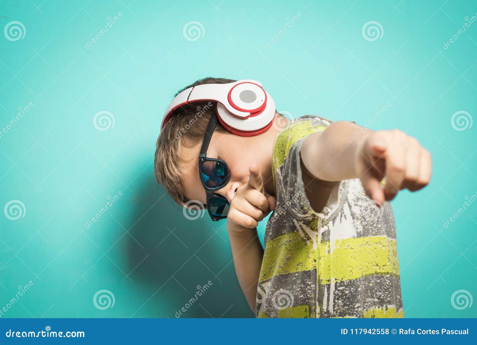 Kind met hoofdtelefoons van muziek en grappige uitdrukking