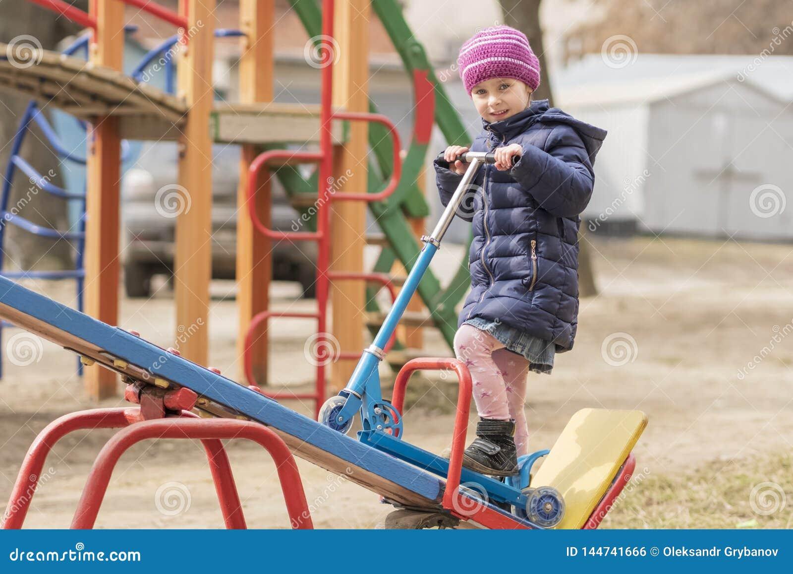 Kind met schopautoped op de speelplaats