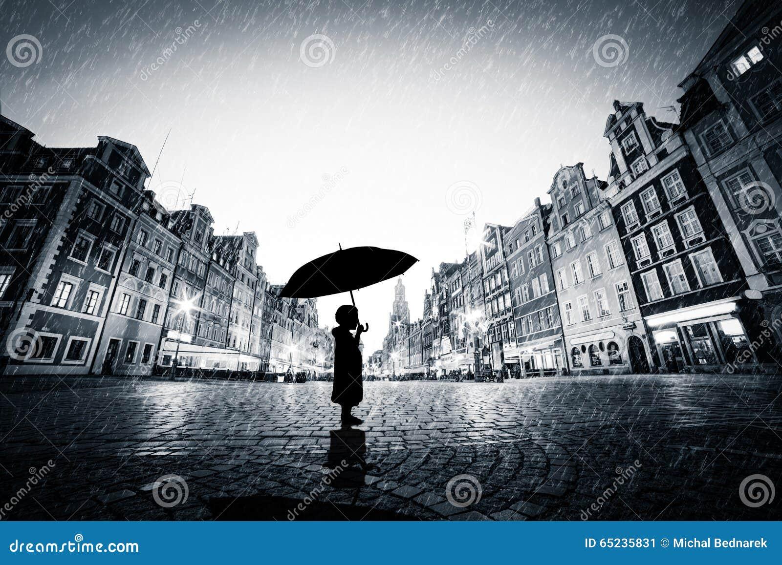 kind mit dem regenschirm der allein auf alter stadt des kopfsteins im regen steht stockbild. Black Bedroom Furniture Sets. Home Design Ideas