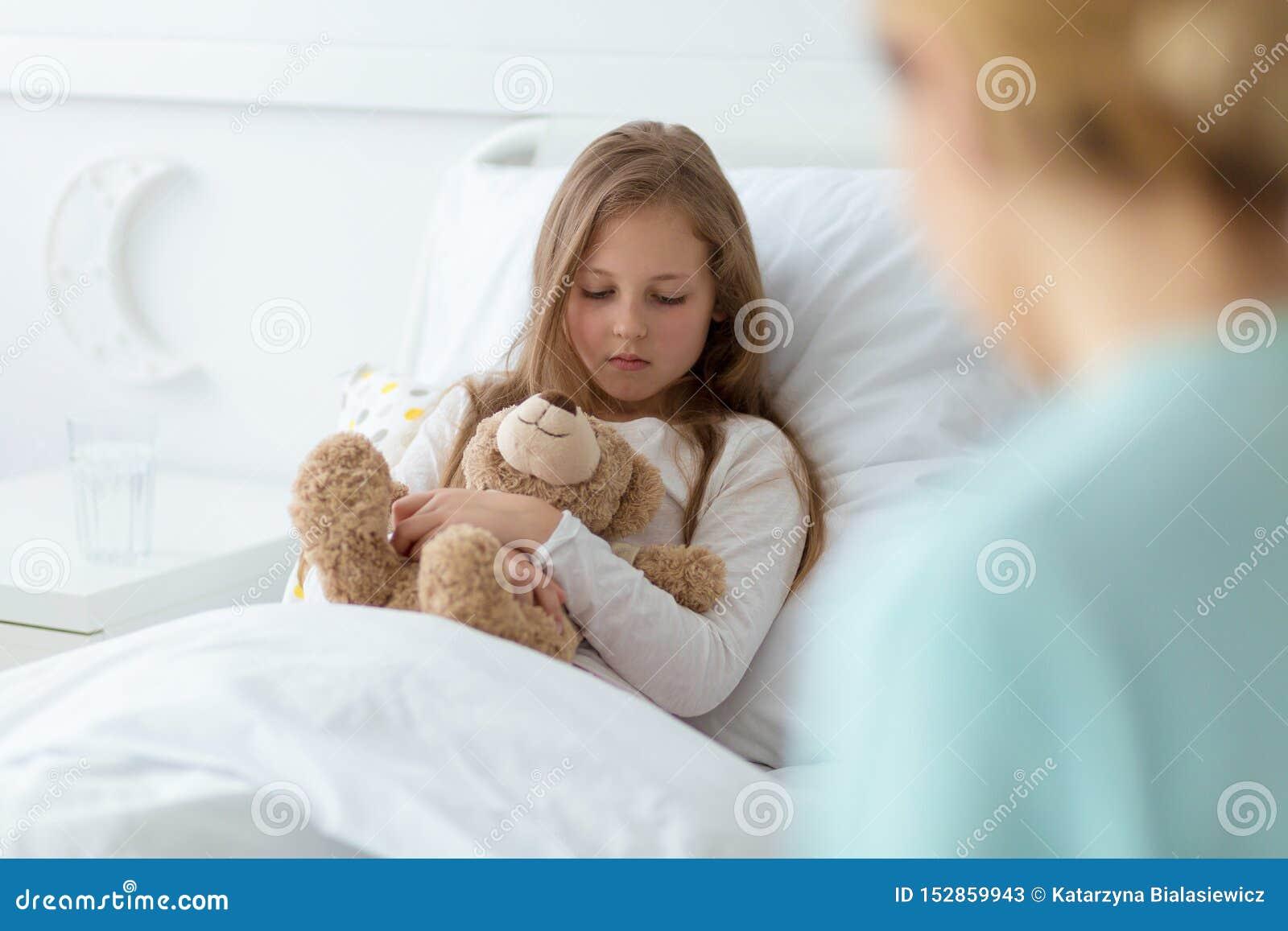 Kind mit einem Teddybären ängstlich von einer Diagnose
