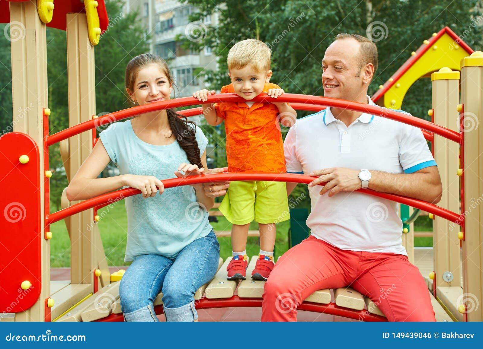 Kind mit Eltern am Spielplatz Mutter, Vati und Sohn Spielen der Familie