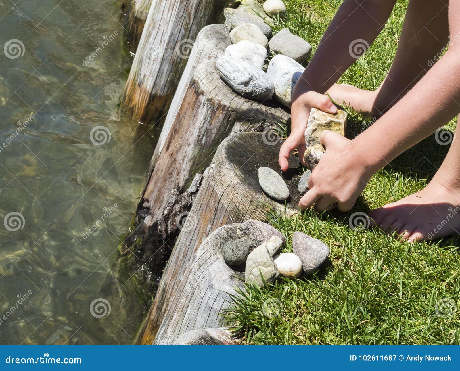 Kind-` s übergibt Spiel mit Steinen auf dem Wasser