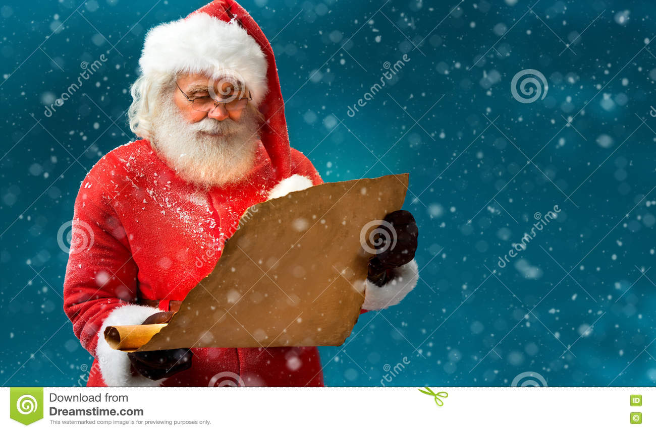 Kind Santa Claus reading vintage paper with wishes.
