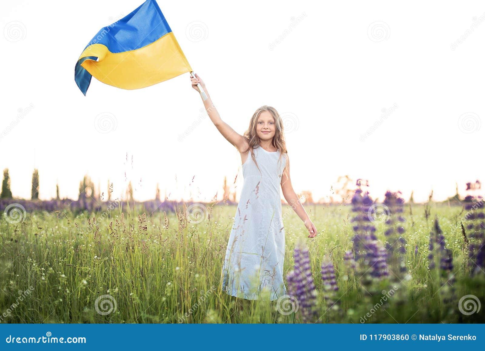Kind trägt flatterndes Blau und gelbe Flagge von Ukraine auf dem Lupinegebiet Ukraine& x27; s-Unabhängigkeitstag Feierlicher Hint