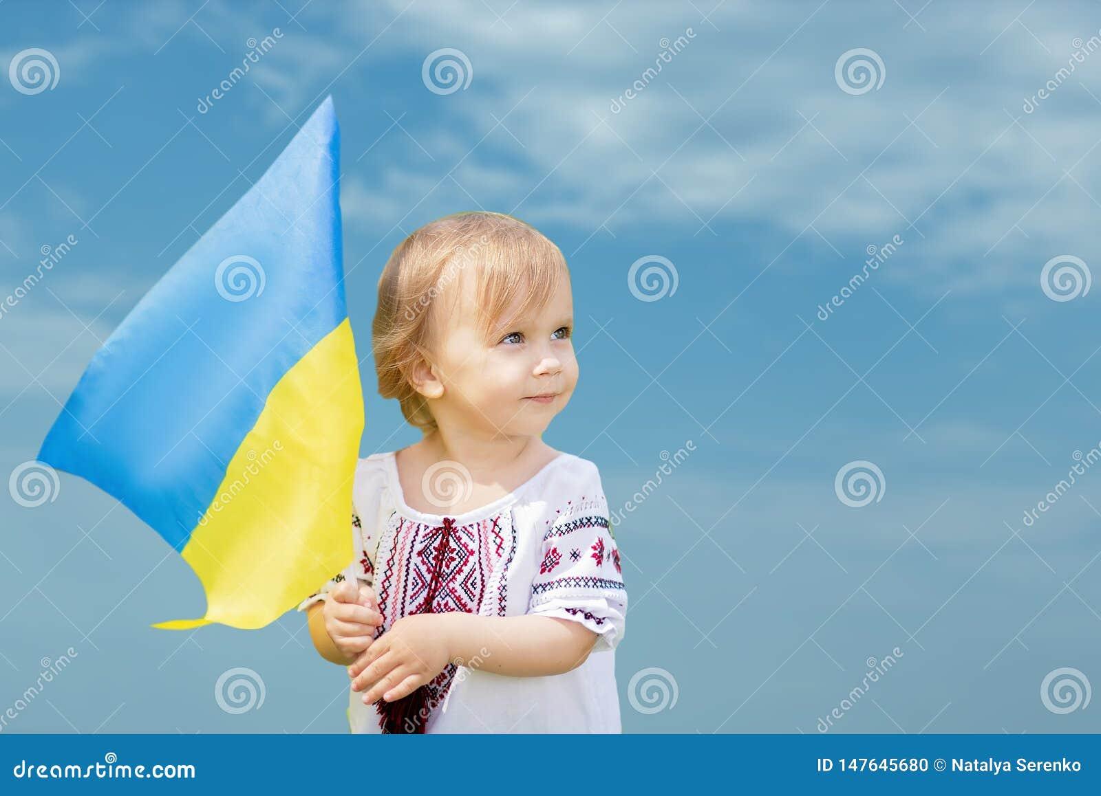 Kind tr?gt flatterndes Blau und gelbe Flagge von Ukraine auf dem Gebiet Ukraine-` s Unabh?ngigkeitstag Feierlicher Hintergrund mi