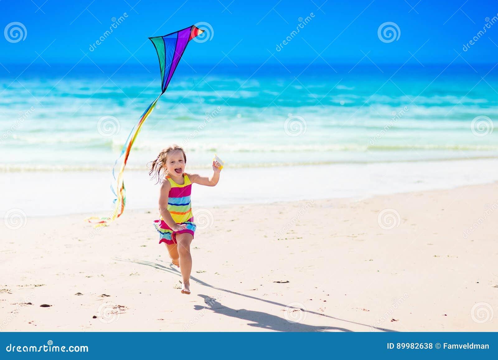 Kind vliegende vlieger op tropisch strand