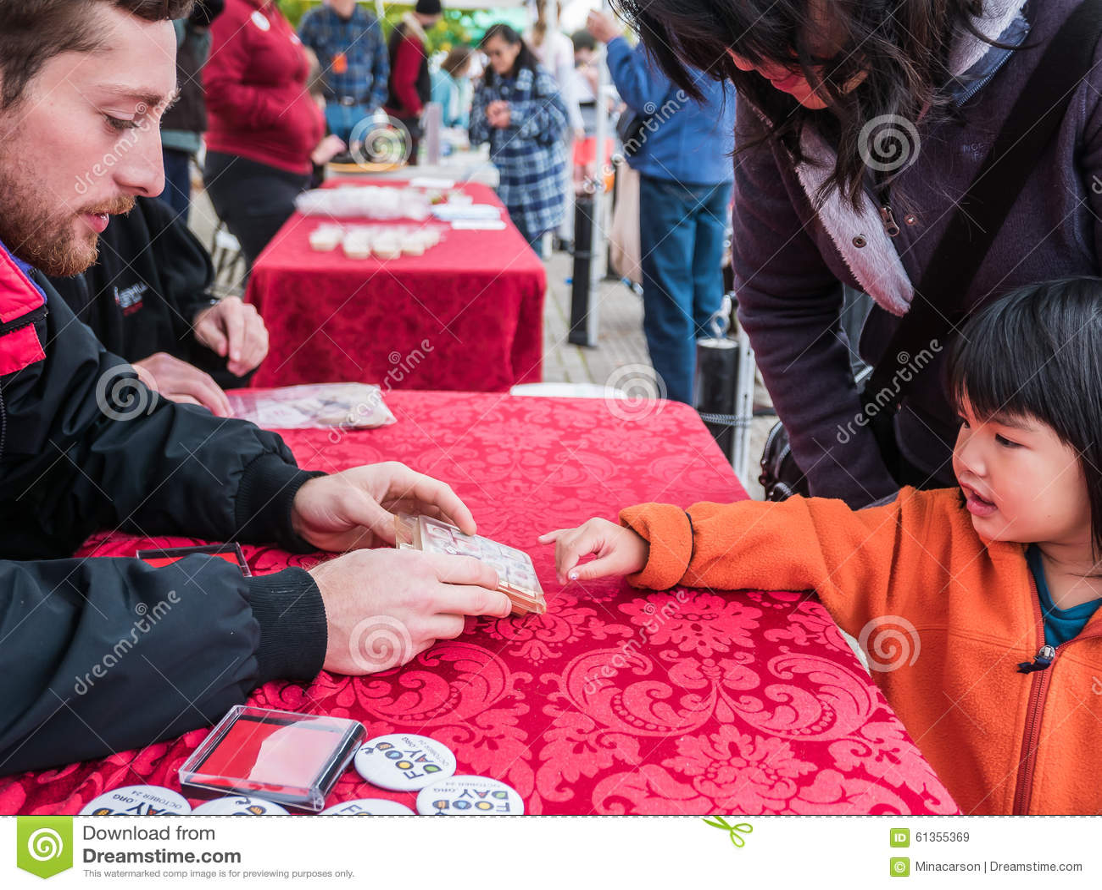 Kind wählt Handstempel vom Lebensmittel-Tagesfreiwilligen