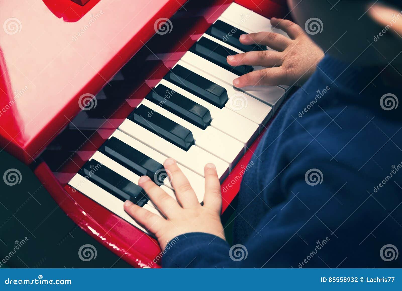 Kind, welches das Klavier spielt