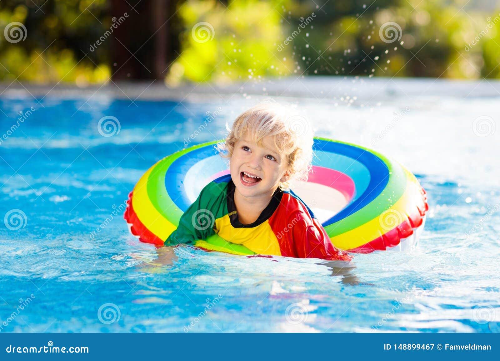 Kind in zwembad op stuk speelgoed ring De jonge geitjes zwemmen