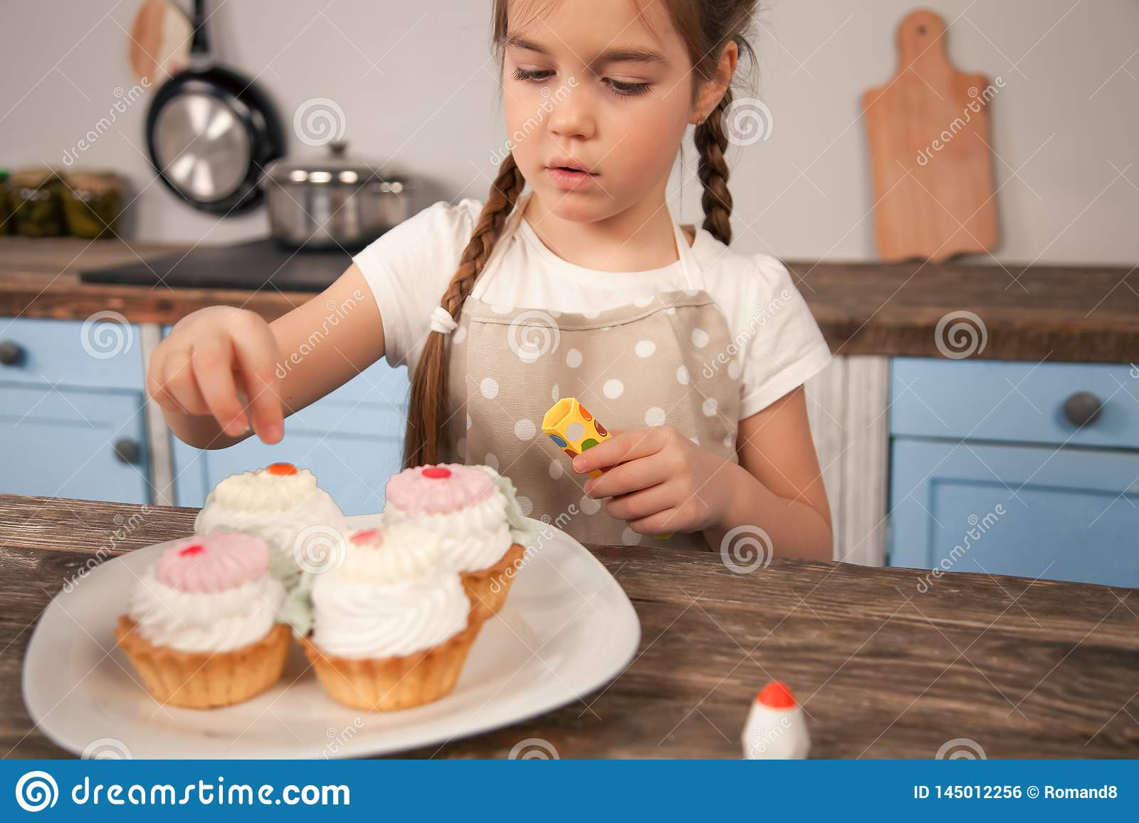 Kinddochter in de keuken die cakes verfraaien wordt zij gemaakt met haar mamma weinig helper, eigengemaakt voedsel