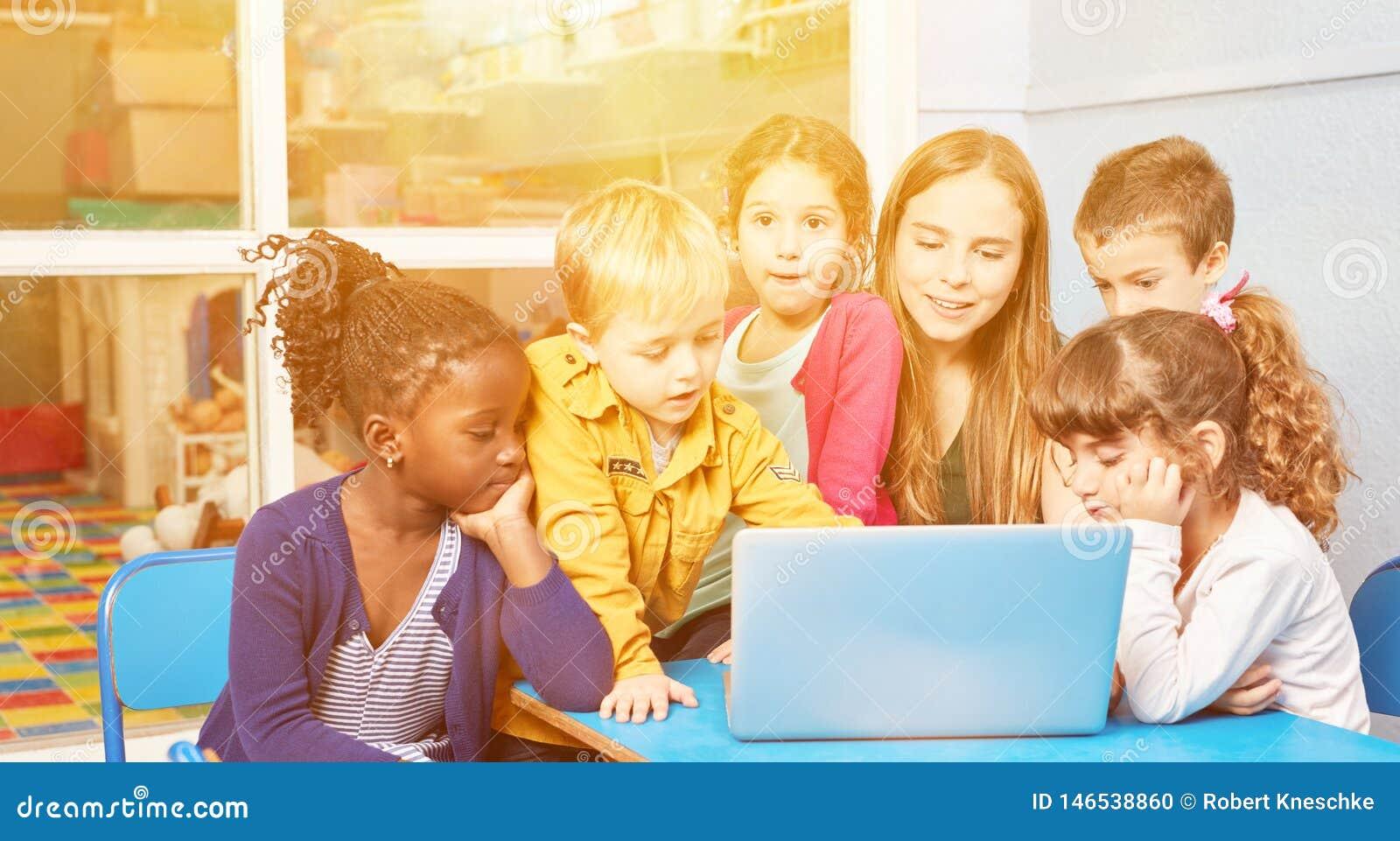 kinder am computer mit erzieher im kindergarten stockfoto