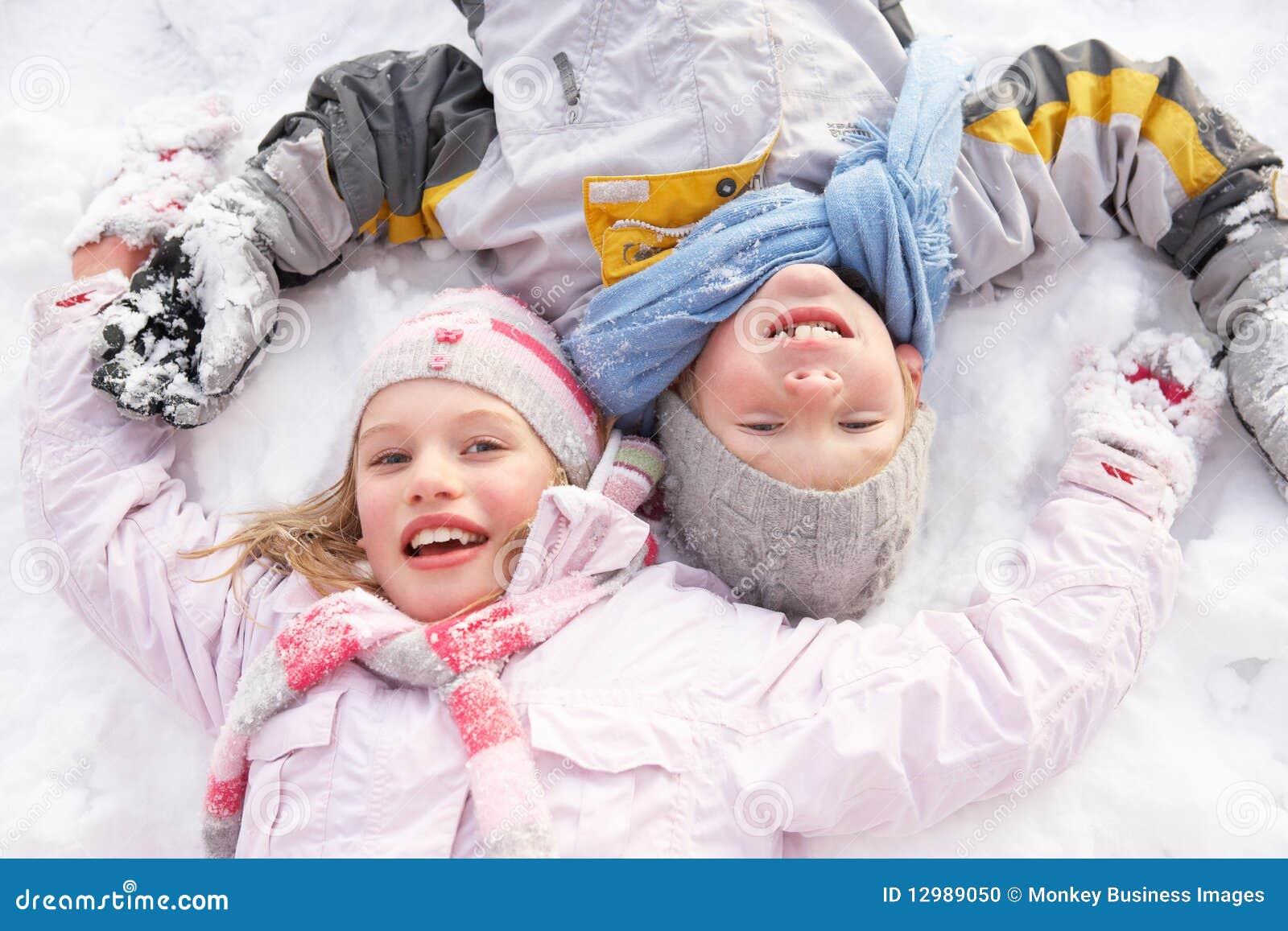 Kinder, die auf Boden bildenschnee-Engel legen