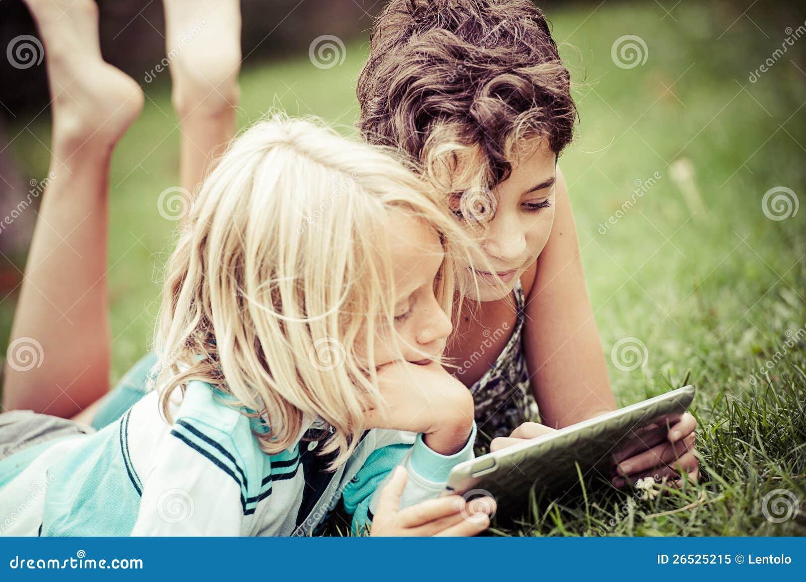 Kinder, die auf dem Gras schaut auf der Tablette liegen