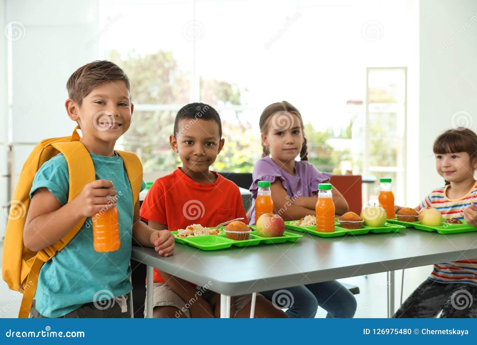 Kinder, die bei Tisch sitzen und gesundes Lebensmittel essen