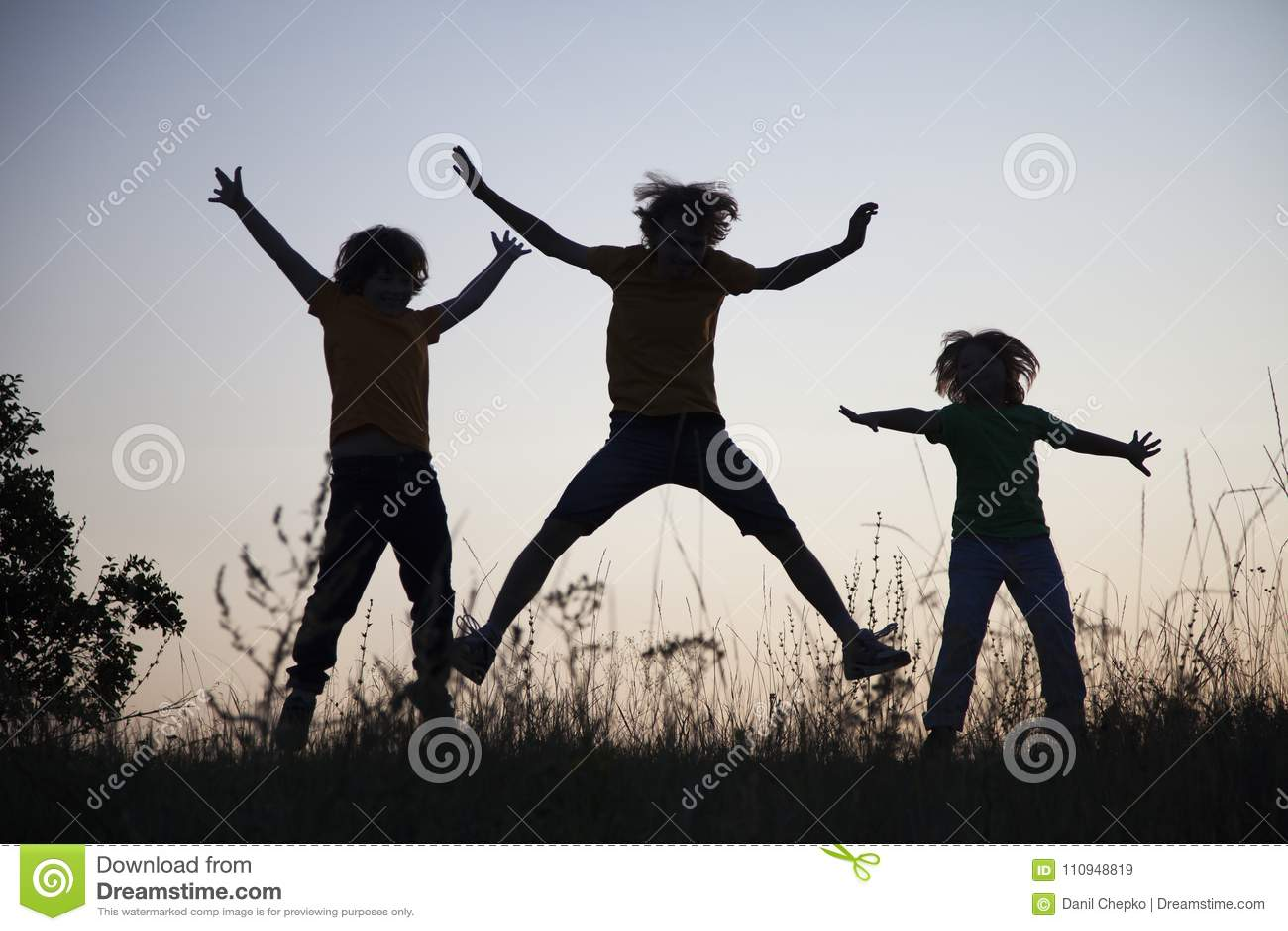 Kinder, die das Springen auf die Sommersonnenuntergangwiese silhouettiert spielen