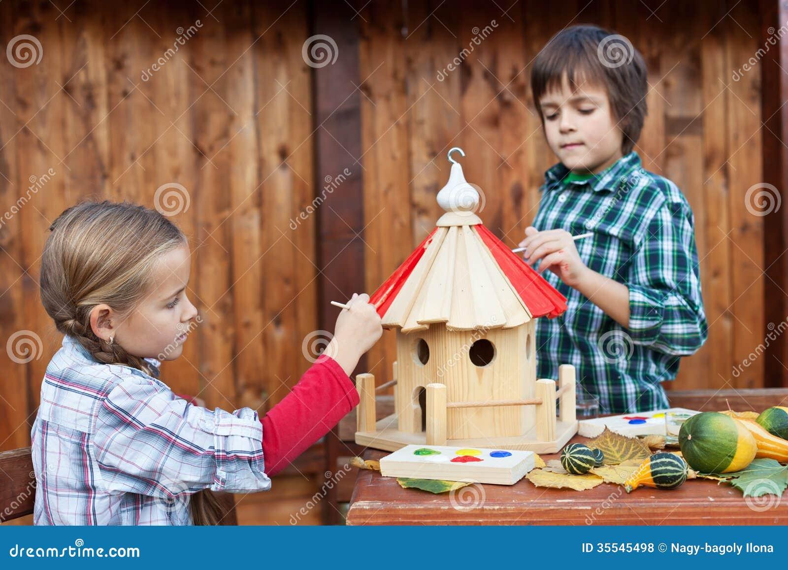 Die kinder die das vogelhaus für den winter malen interessieren