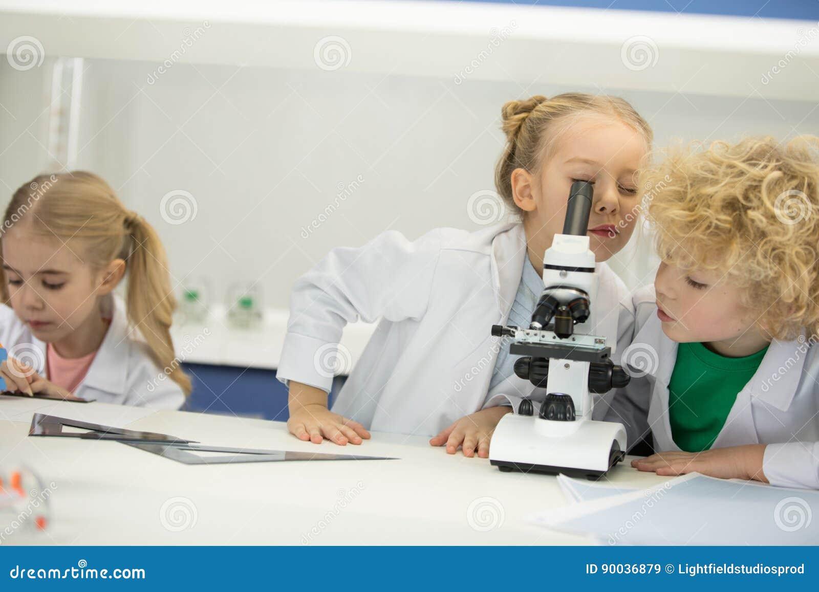 Kinder die durch mikroskop in der wissenschaftsklasse schauen