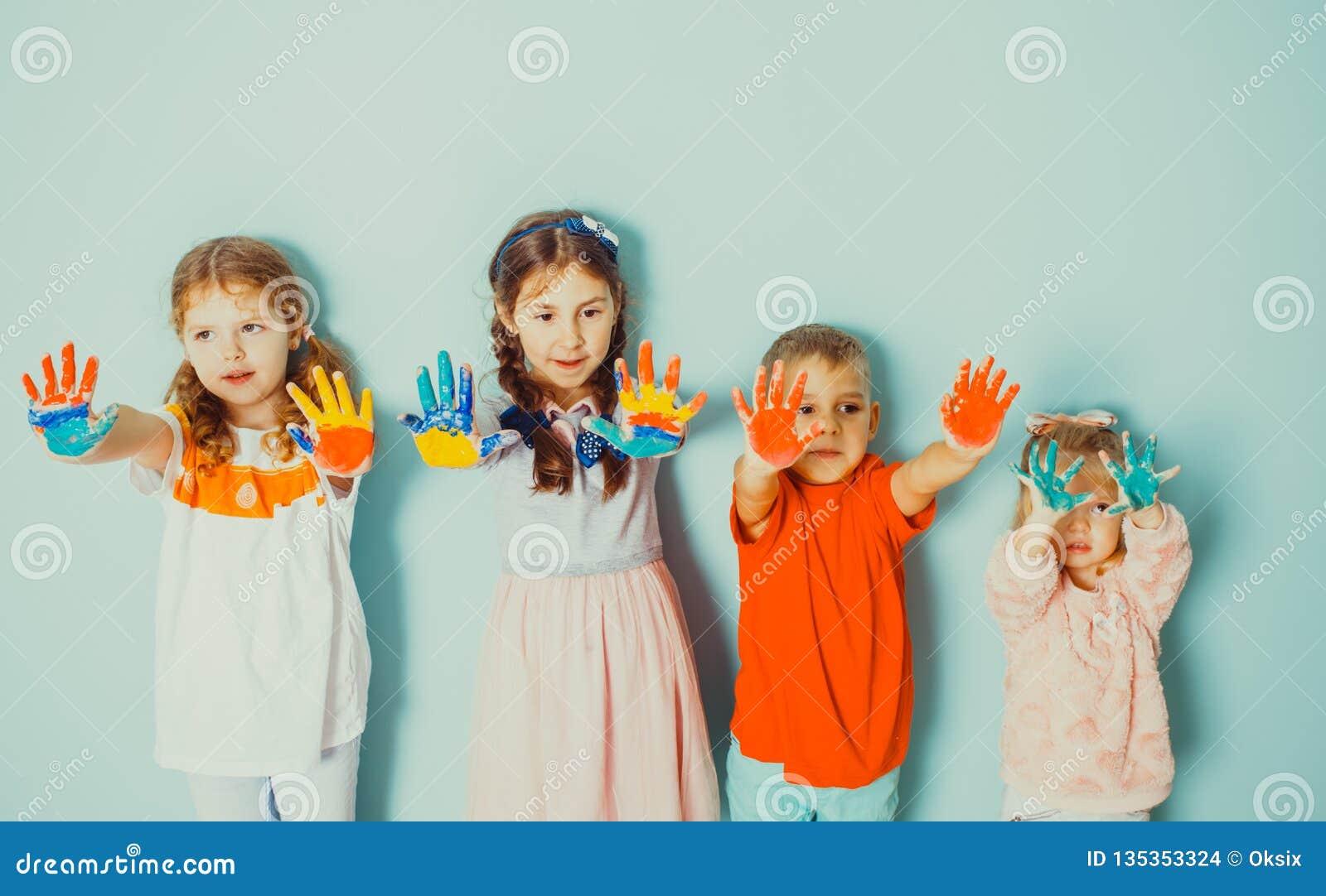 Kinder, die ihre gemalten bunten Hände zur Kamera zeigen