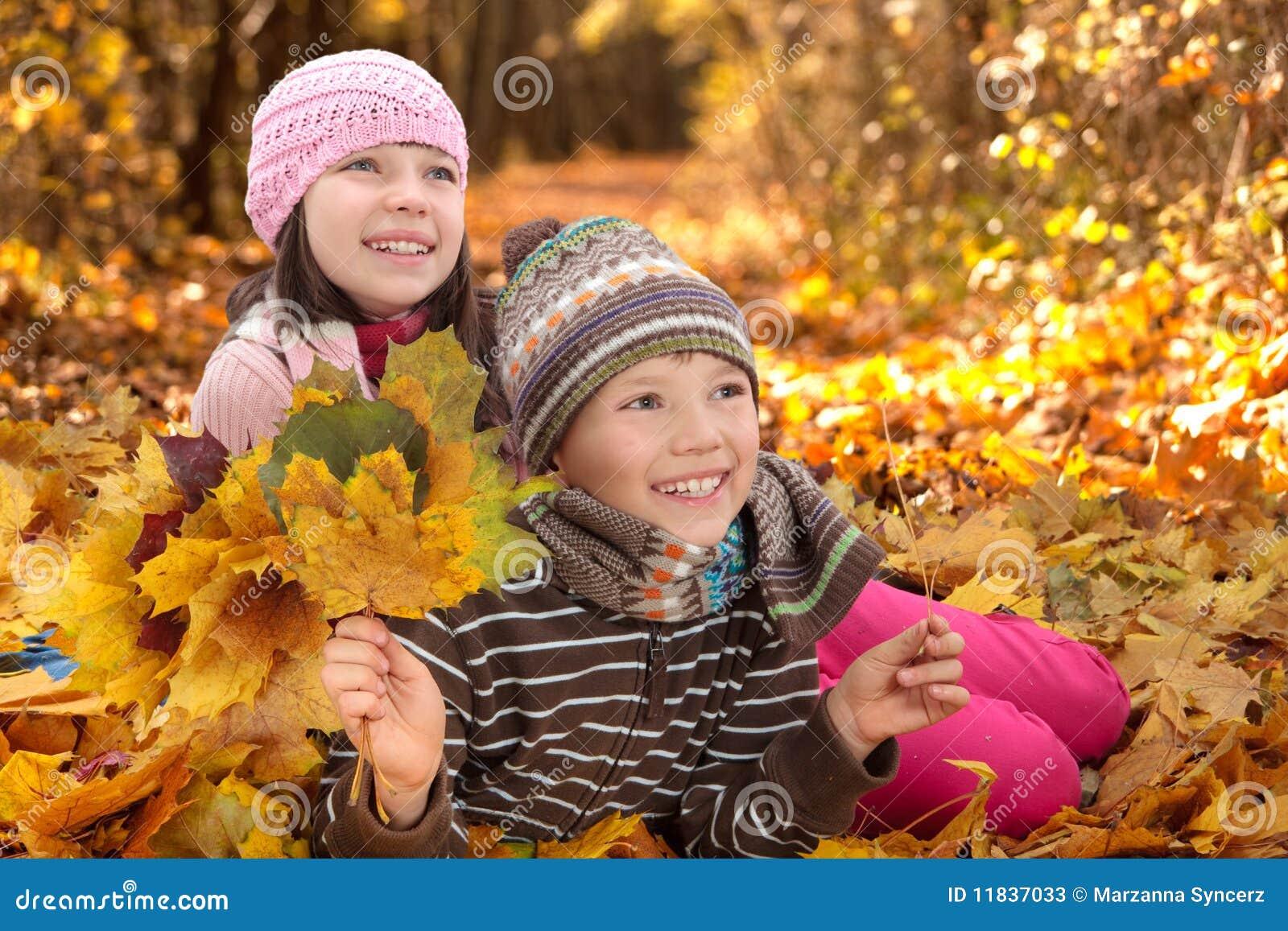 Kinder, die im Herbst spielen