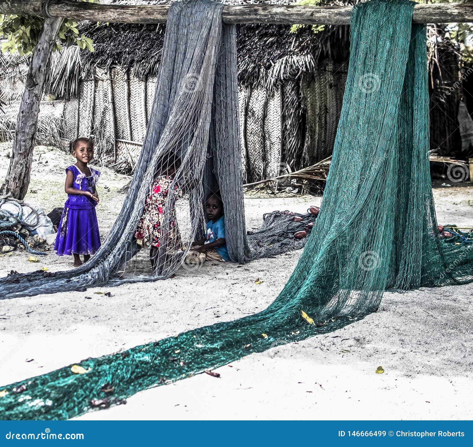 Kinder, die mit Fisch-Netzen in Sansibar spielen