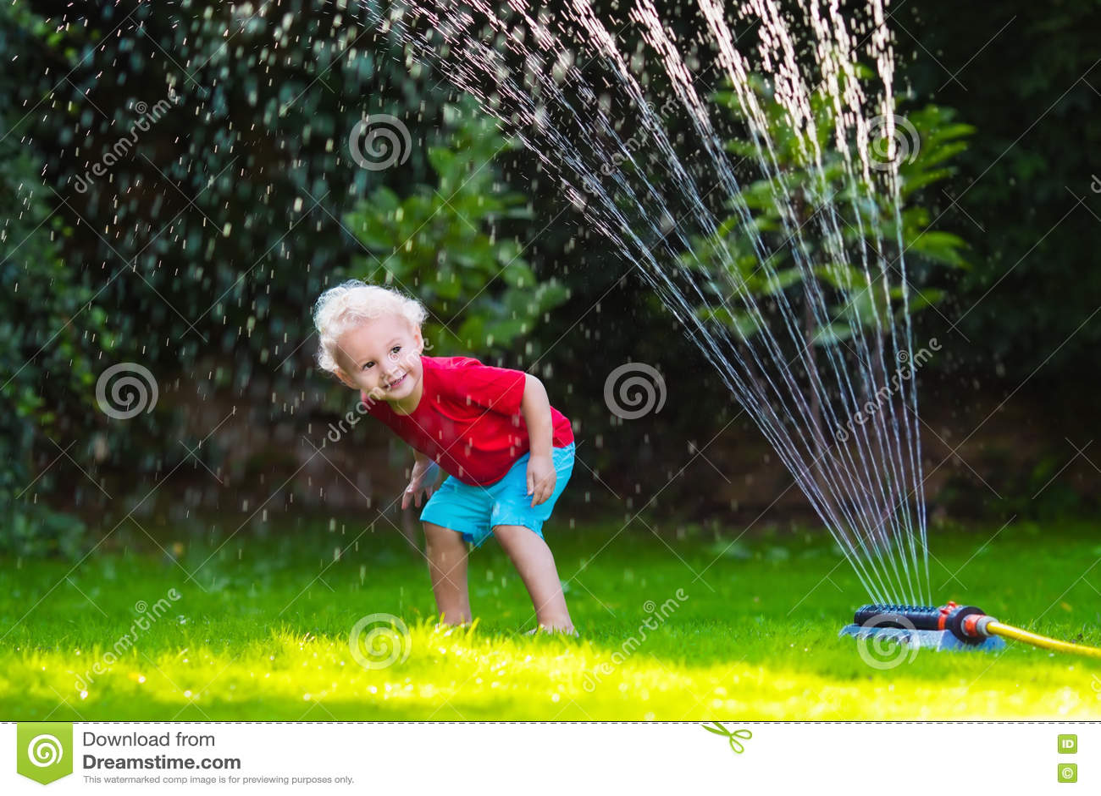Kinder, die mit Gartenberieselungsanlage spielen