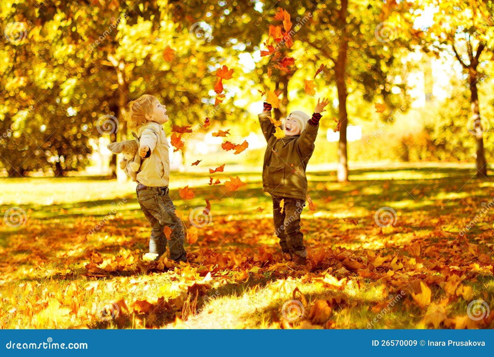 Kinder, die mit Herbst gefallenen Blättern im Park spielen