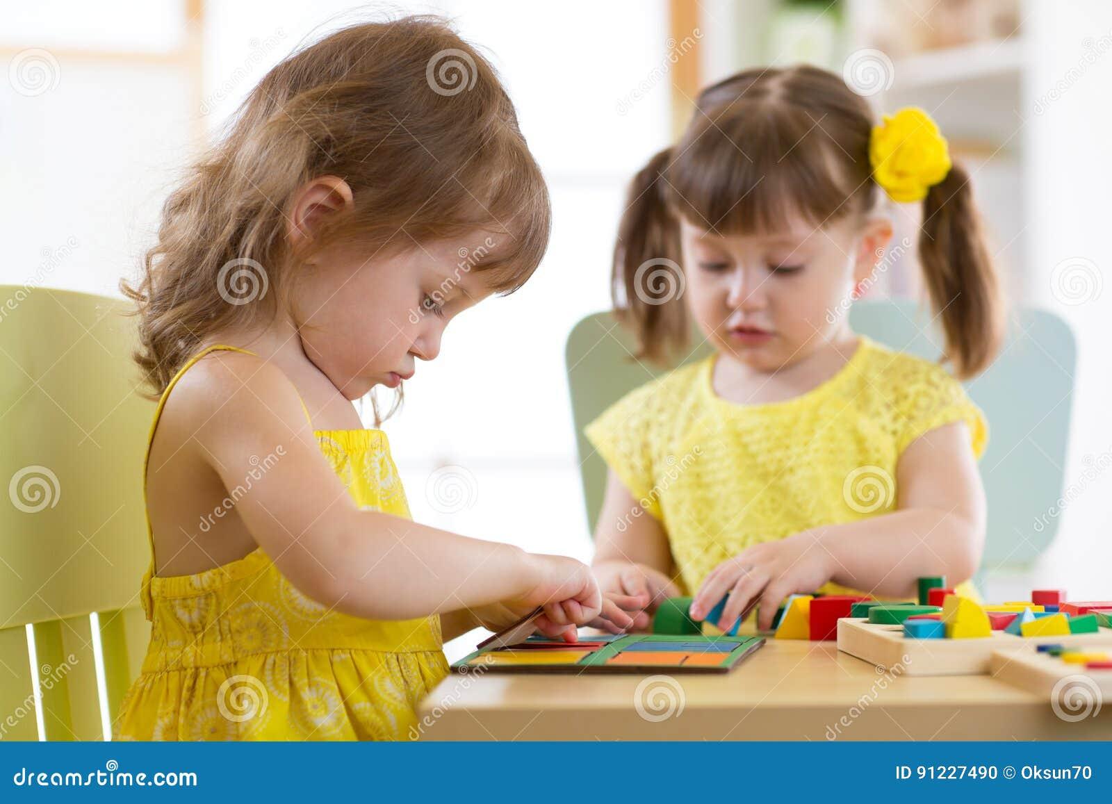 kinder die mit logischem spielzeug auf schreibtisch im kindertagesst ttenraum oder. Black Bedroom Furniture Sets. Home Design Ideas