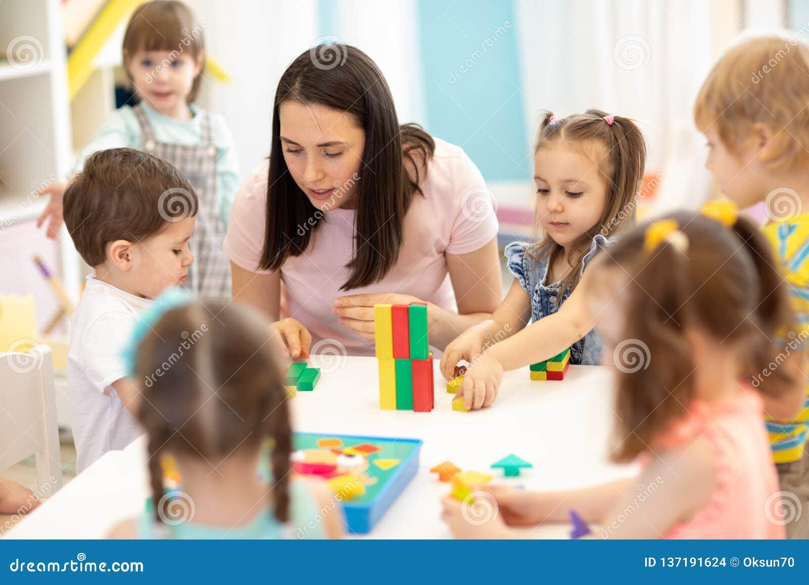 Kinder, die mit pädagogischen Spielwaren im Kindergarten spielen Kindergärtnerin, die um Kinder sich kümmert