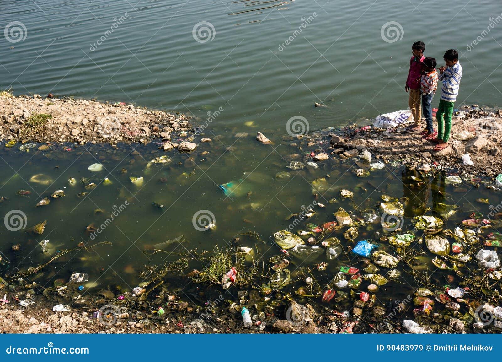 Kinder, die nahe schmutzigem verunreinigt mit dem Rückstand des Sees, die Fische aufpassend spielen