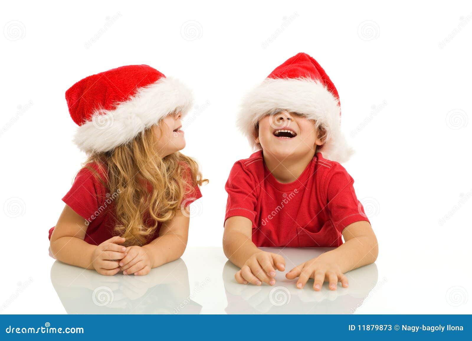 Kinder, die Spaß mit Weihnachtshüten haben