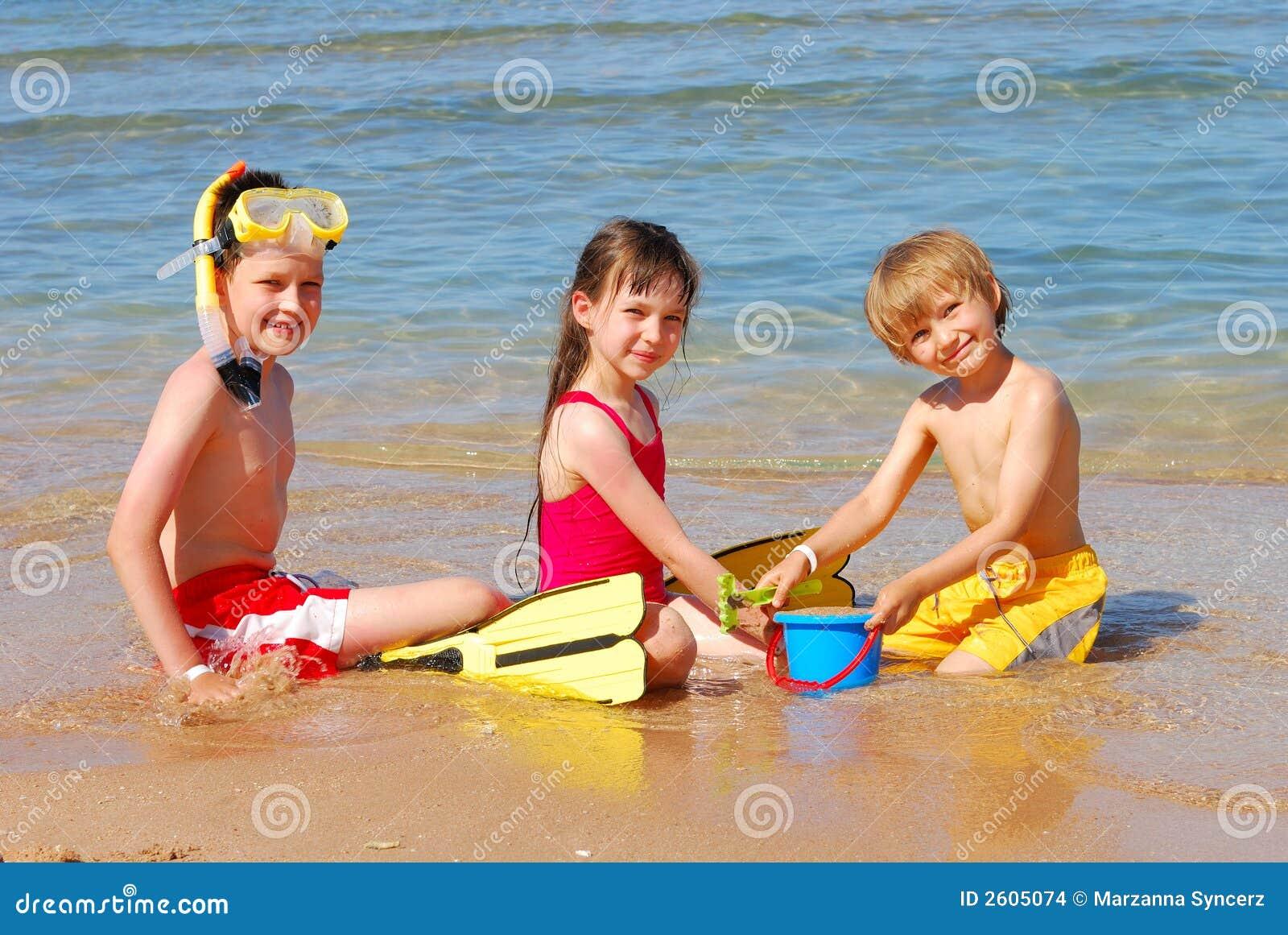 Kinder, die am Strand spielen
