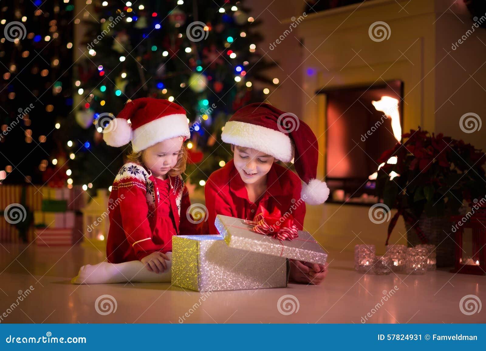 Weihnachtsgeschenke Für Familie.Kinder Die Weihnachtsgeschenke Am Kamin öffnen Stockbild Bild Von