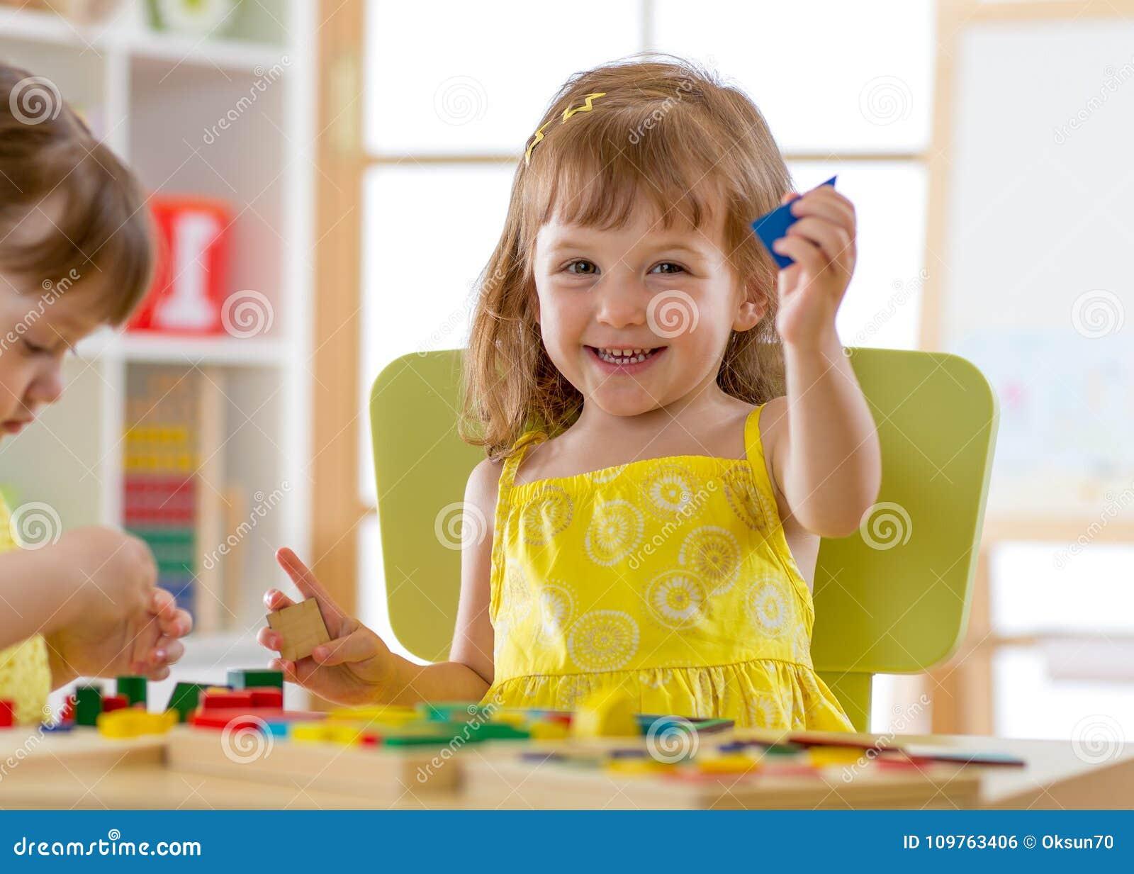 Kinder, die zu Hause mit Entwicklungsspielwaren oder Kindergarten oder Kindertagesstätte spielen