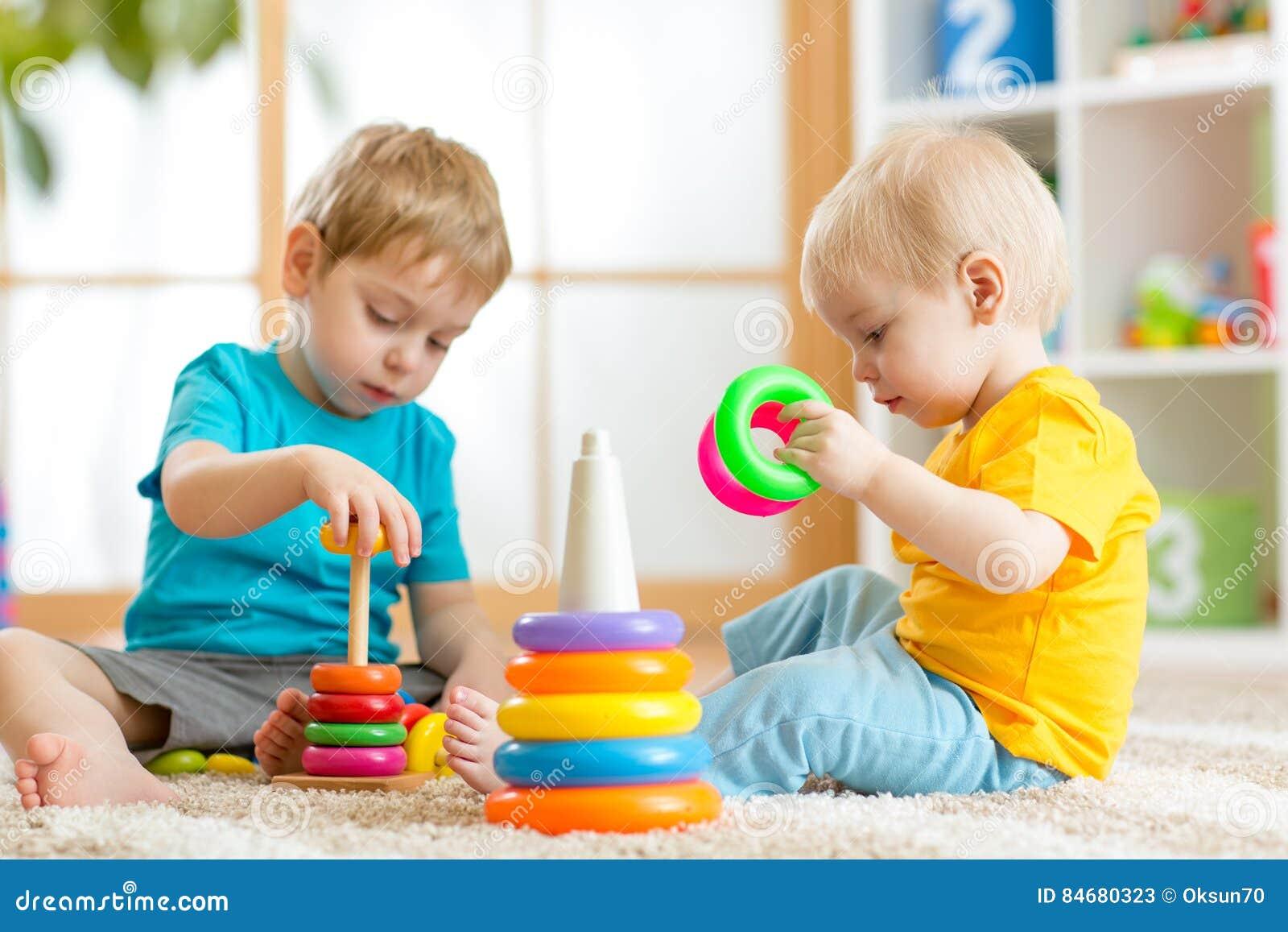 Kinder, die zusammen spielen Kleinkindkind und Babyspiel mit Blöcken Pädagogische Spielwaren für Vorschulkindergartenkind