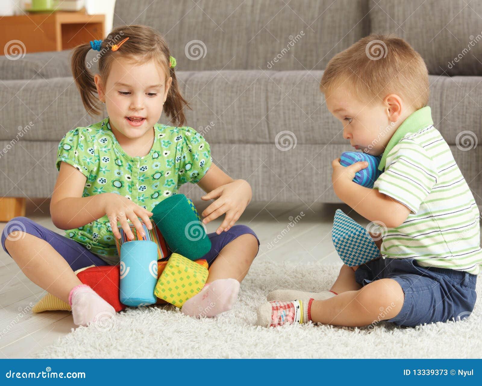 Jahre alte kinder die zusammen zu hause auf dem fußboden spielen